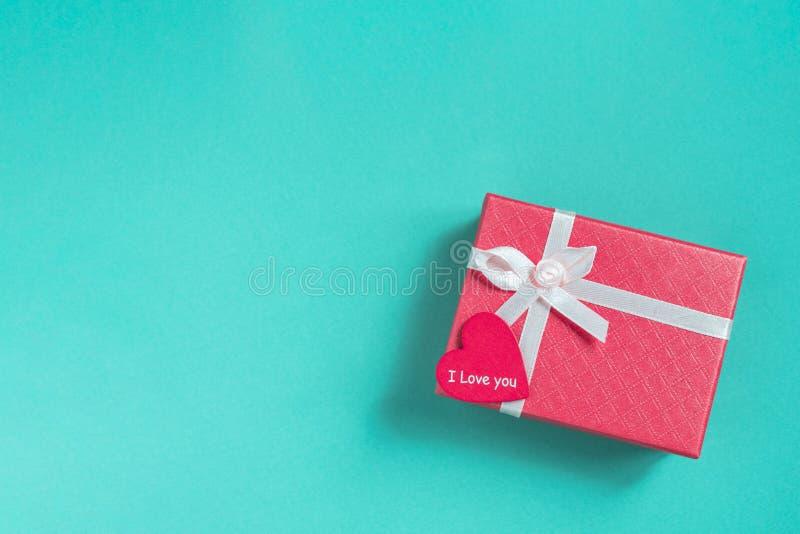 Rosa Geschenkbox mit rotem Herzen auf aquamarinem Hintergrund lizenzfreie stockfotos