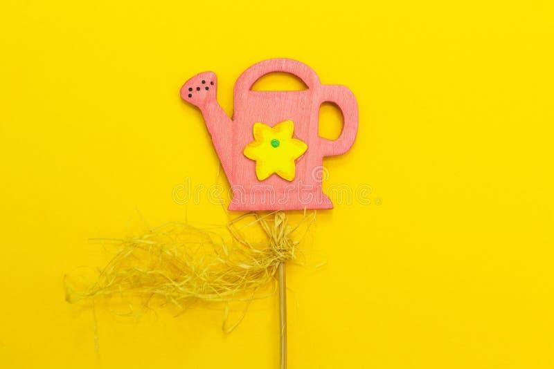 Rosa Gießkanne auf einem gelben Hintergrund, Garten funktioniert stockfotos
