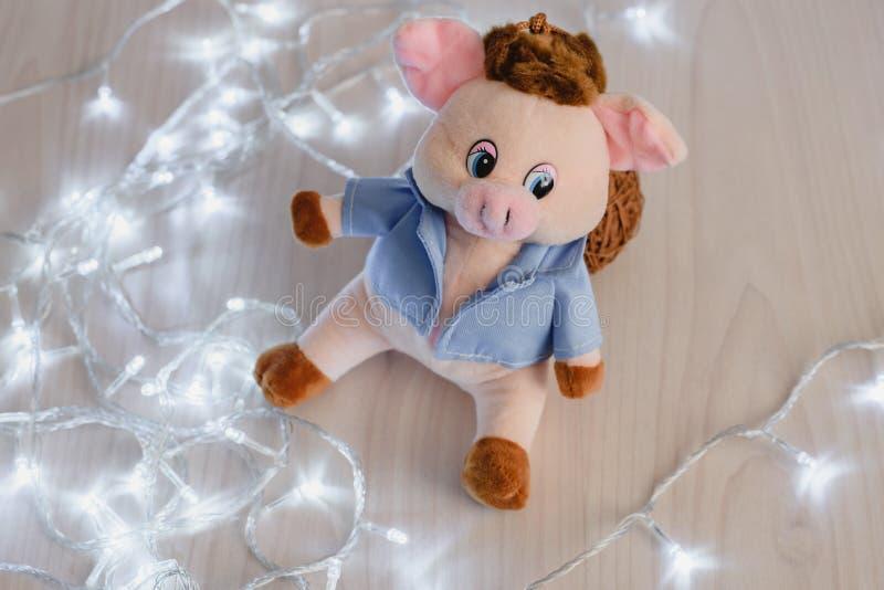 Rosa glückliches Ferkel des Stilllebens und LED-Feiertagsgirlande auf hölzernem Hintergrund, guten Rutsch ins Neue Jahr stockbild