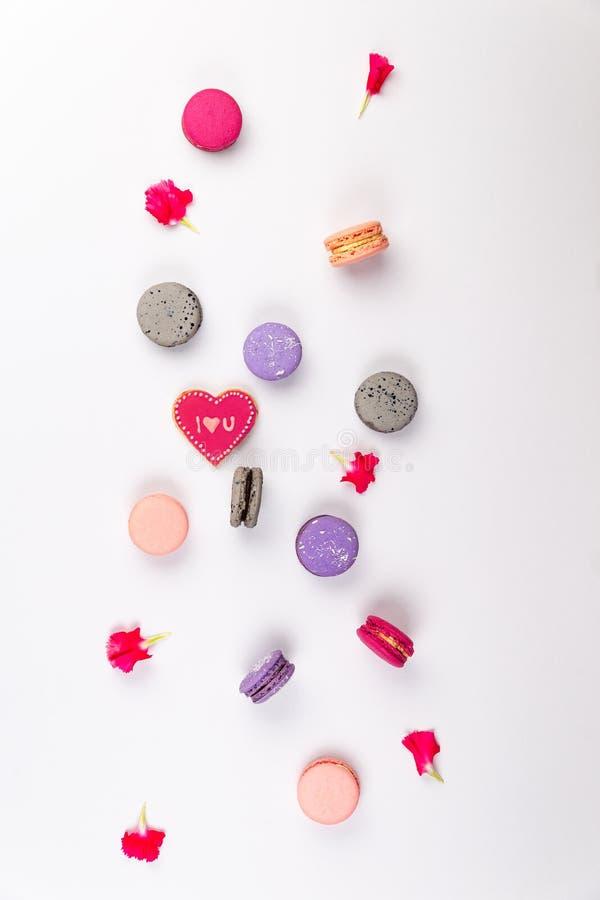 Rosa, gråa och purpurfärgade franska makron med älskar jag dig kakan, och rosa inkarnationkronblad fördelar på en vit bakgrund i  arkivbild