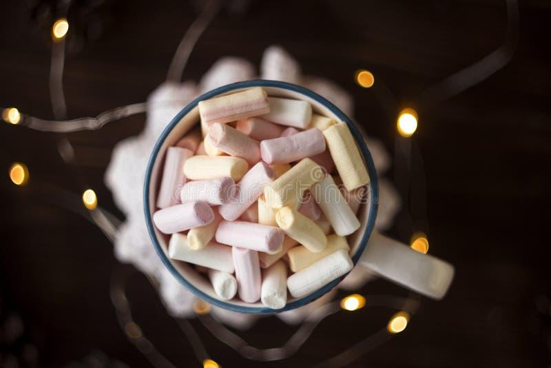 Rosa, gul och vit marshmallow i koppen, bästa sikt, julljus, bakgrund royaltyfri bild