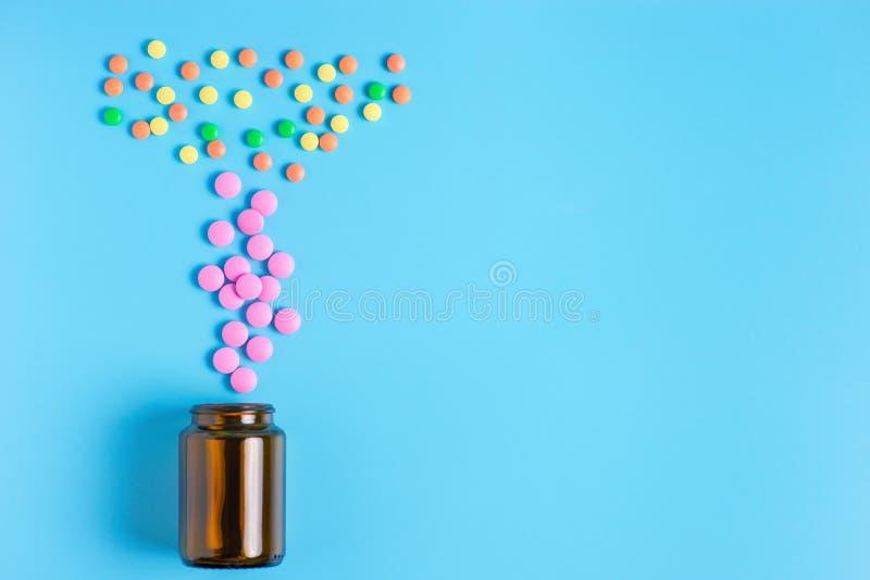Rosa, gula och gröna piller i glasflaskan på en blå bakgrund royaltyfri bild