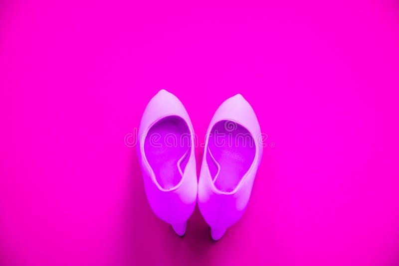 Rosa höga heeled skor på rosa purpurfärgad bakgrund - bästa sikt - häl som pekar upp royaltyfri fotografi