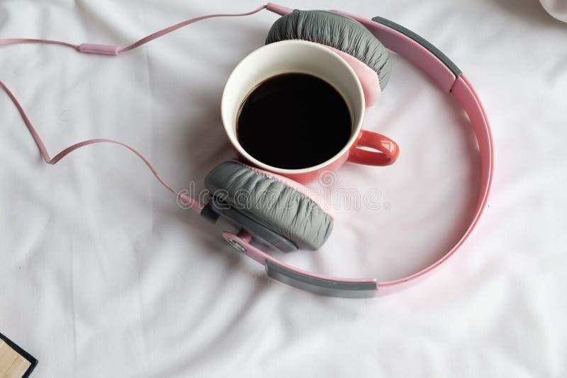 Rosa handphone und roter Tasse Kaffee auf Bett morgens stockfotos