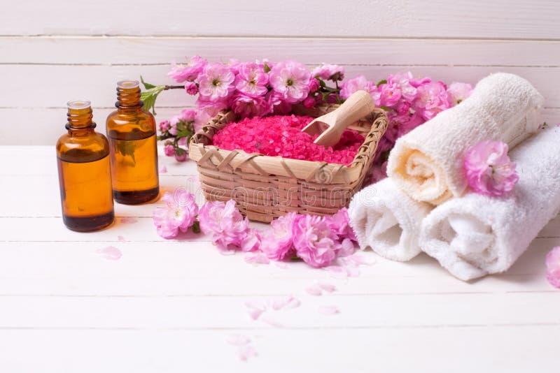 Rosa hav som är salt i bunke, handdukar, flaskor med aromoljor och stift royaltyfri foto