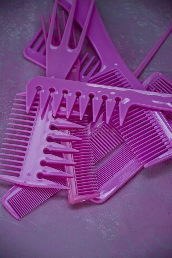 Rosa heller Kamm f?r Friseure Sch?nheits-Saal Werkzeuge f?r Frisuren Bunter rosafarbener Hintergrund friseursalon Ein Satz von un stockfotos