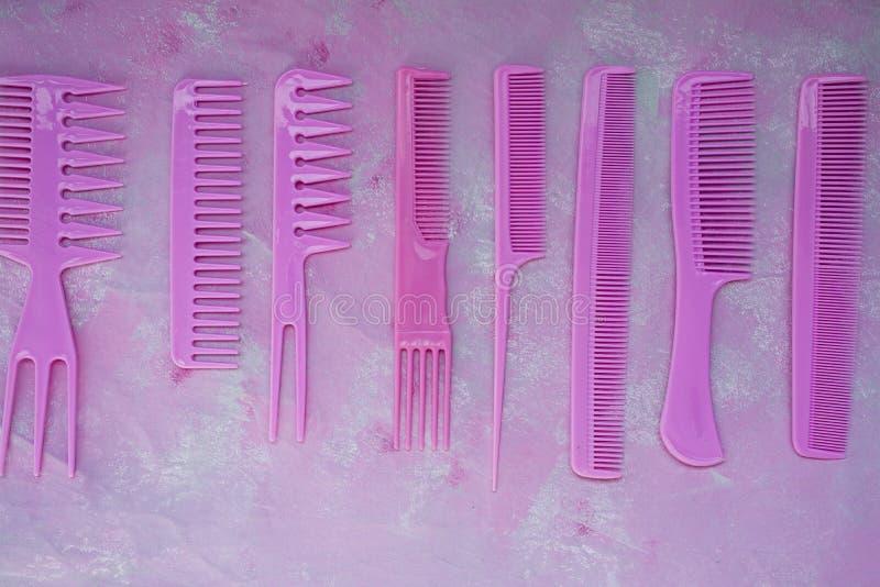 Rosa heller Kamm f?r Friseure Sch?nheits-Saal Werkzeuge f?r Frisuren Bunter rosafarbener Hintergrund friseursalon Ein Satz von un lizenzfreie stockfotos