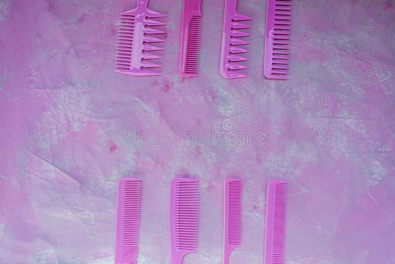 Rosa heller Kamm f?r Friseure Sch?nheits-Saal Werkzeuge f?r Frisuren Rosa Hintergrund friseursalon Satz verschiedene Haarb?rsten stockfotografie