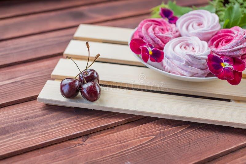 Rosa hemlagad sefir eller marshmallow med det körsbärsröda bäret och blommor på ljus träbakgrund Marshmallow maräng arkivfoton