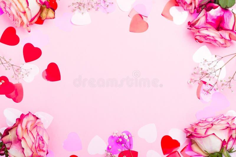 Rosa hermosa del rosa, corazones decorativos del confeti y cinta rosada en fondo rosado del día de tarjetas del día de San Valent foto de archivo