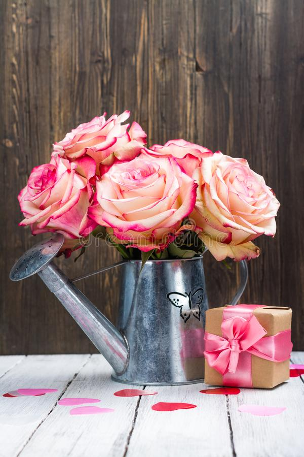 Rosa hermosa del rosa en una regadera de la lata en fondo de madera fotos de archivo libres de regalías