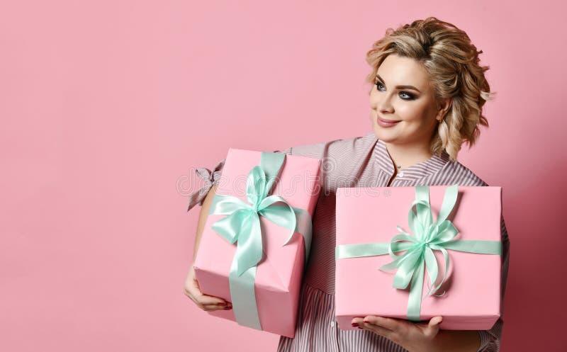 Rosa hermoso del control dos de la mujer y cajas de regalo verdes en colores pastel de los regalos de Navidad para la sonrisa de  fotografía de archivo libre de regalías