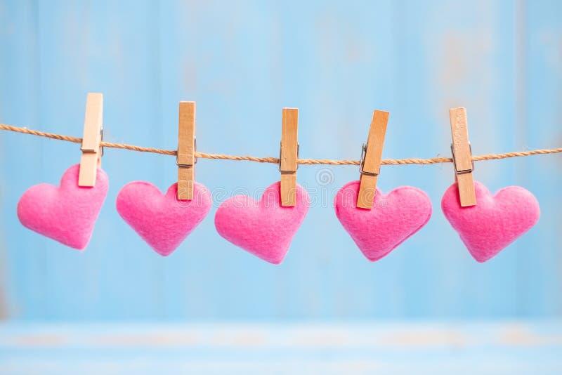 Rosa Herzformdekoration, die an der Linie mit Kopienraum für Text auf blauem hölzernem Hintergrund hängt Liebe, Hochzeit, romanti lizenzfreies stockbild