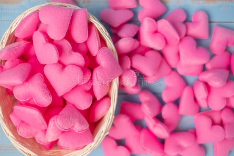 Rosa Herzformdekoration im Korb auf blauem Holztischhintergrund Der Hochzeit, romantischen und glücklichen Valentine' s Tag der stockbild
