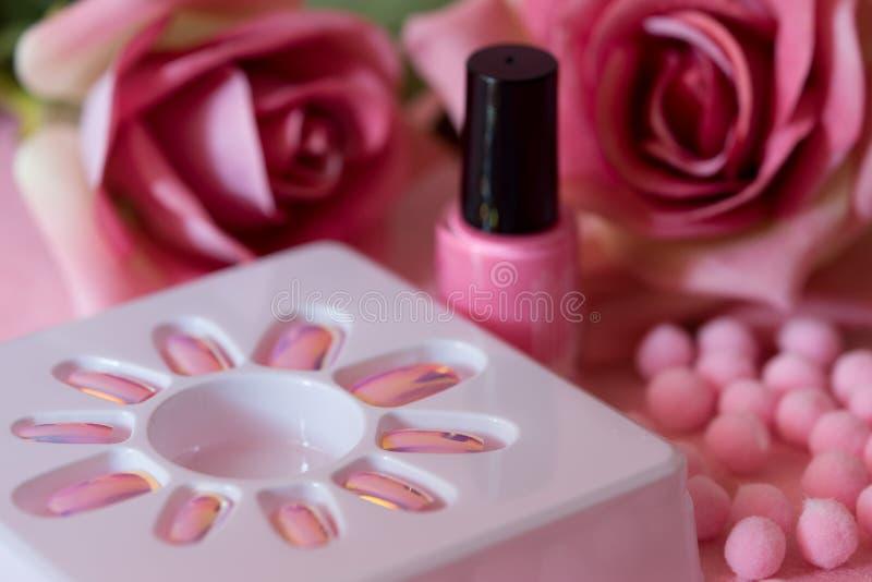 Rosa Hintergrund des Nagellacks und der Rosen lizenzfreie stockbilder