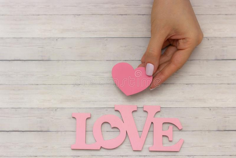 Rosa hjärta i handcloseup på träbakgrund, nära ordet - förälskelse arkivfoto