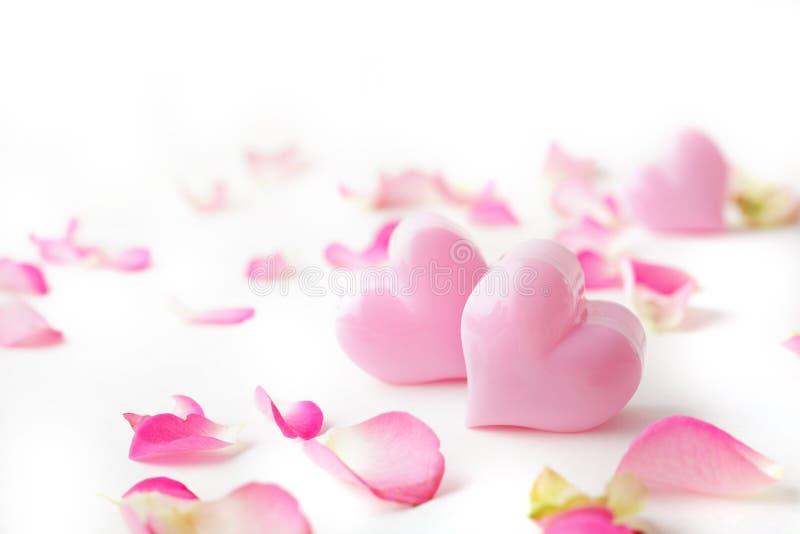 Rosa hjärta och rosa kronblad arkivbilder