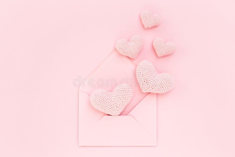 Rosa hjärtor för valentin` s i kuvert, förälskelsebikt arkivfoto
