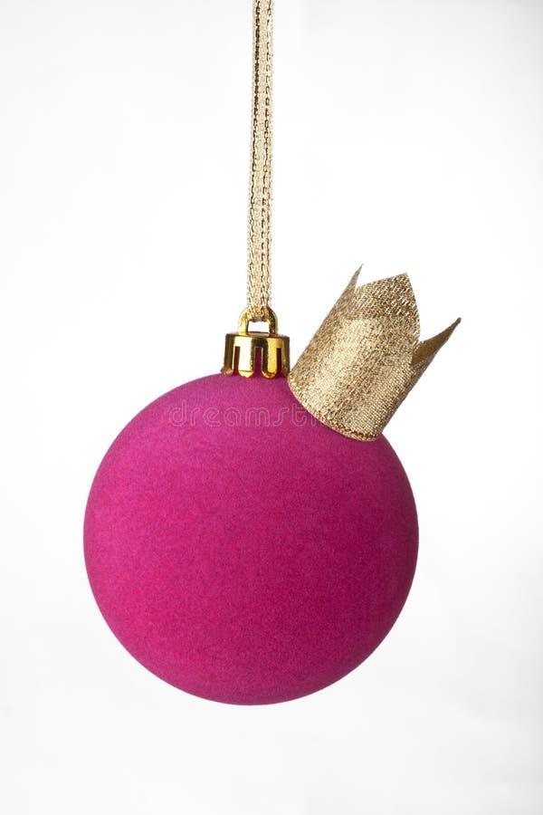Rosa julboll som hänger på guld- band med en krona arkivfoton