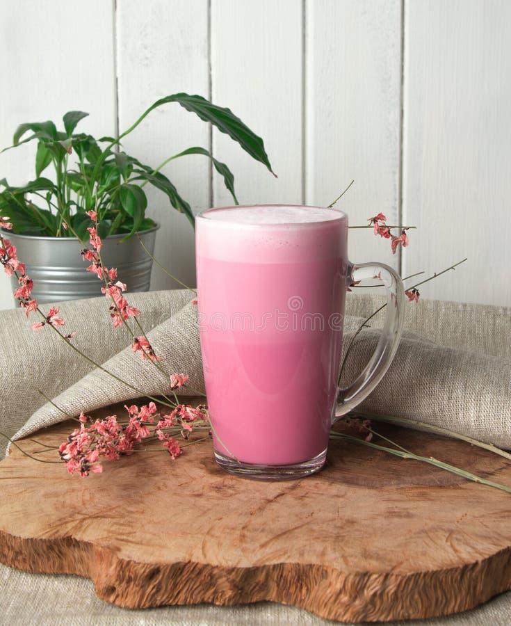 Rosa Kaffee Latte macchiato in einer Glasschale auf einem h?lzernen Schutztr?ger verziert mit Trockenblume stockfoto