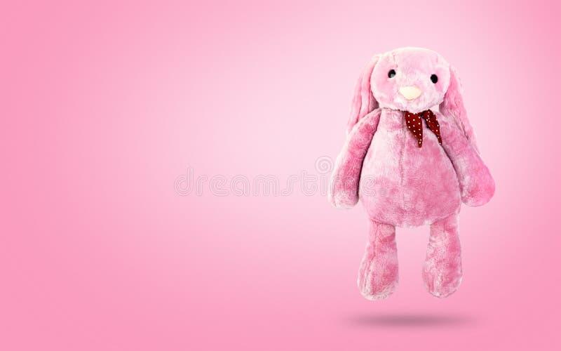 Rosa Kaninchenpuppe mit den großen Ohren auf süßem Hintergrund Nettes Plüschtier und flaumiger Pelz für Kinder stockfotos