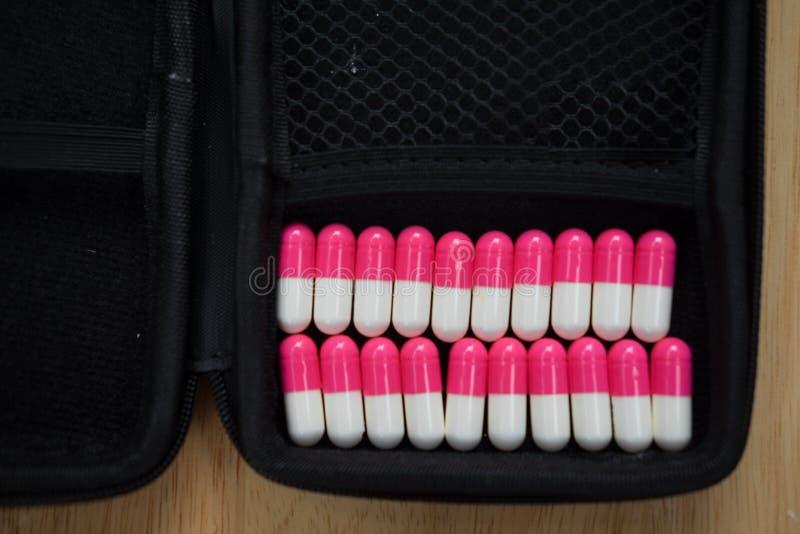 Rosa kapselpiller som är vita och arkivbilder