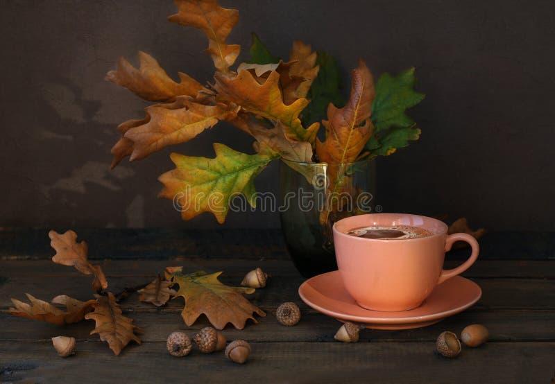 Rosa keramischer Tasse Kaffee, trockene Eichenblätter und Eicheln auf dem alten Holztisch lizenzfreies stockfoto