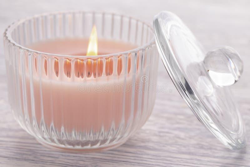 Rosa Kerze, die in einem Glasbecher auf einem alten weißen Holztisch brennt stockfoto