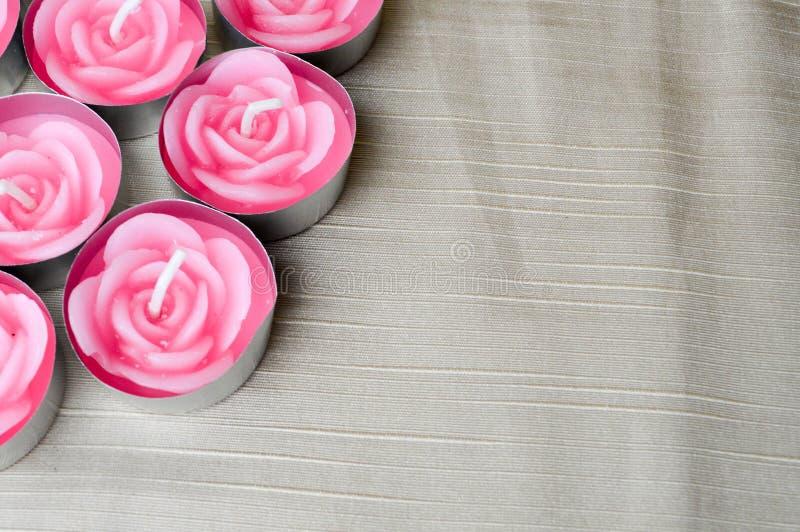 Rosa Kerzen sind in der linken Ecke des Schirmes in Form von Rosen zum Tag von St.-Valentinsgruß auf einem Hintergrund der Beige  lizenzfreie stockfotos
