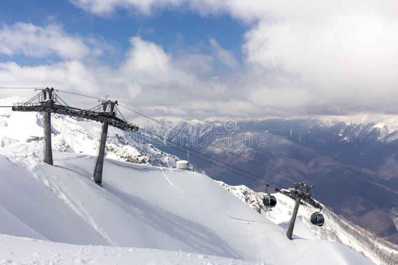 ROSA KHUTOR, ΡΩΣΊΑ - 31 ΜΑΡΤΊΟΥ 2016: Τοπ άποψη βουνών τοπίου από την αιχμή της Rosa και τον ανελκυστήρα σκι καλωδίων στοκ φωτογραφίες