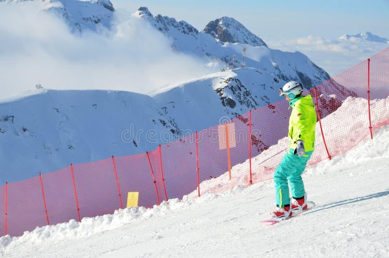 Rosa Khutor, Sochi, Russia, January, 28, 2018, Woman snowboarding on ski resort Rosa Khutor fron Rosa Pik royalty free stock images