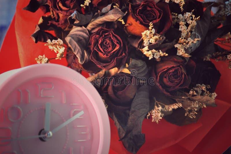 Rosa klocka och torkade röda rosor royaltyfri fotografi