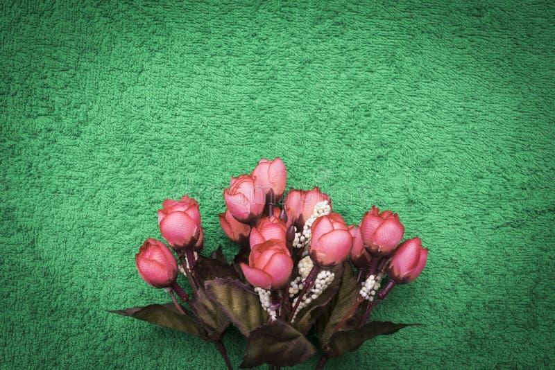 Rosa konstgjorda blommor på ensmaragd bakgrund royaltyfria bilder