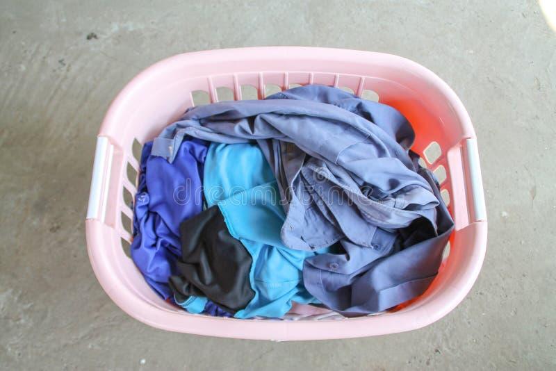 Rosa korg med den smutsiga tvätterit på golv arkivfoto