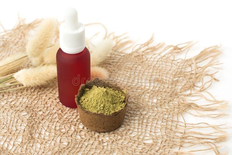 Rosa kosmetisches Flaschen- und Hennastrauchpulver für färbendes Haar, Augenbrauen und mehendi auf einer Leinwand gemacht vom n stockbilder