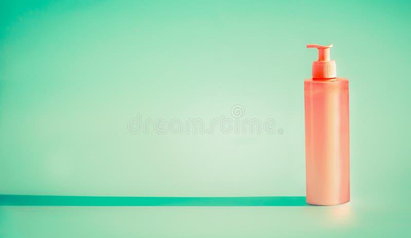 Rosa kosmetisk flaska med utmatarepumpen på mintkaramellbakgrund Lotion för sommarhudomsorg eller sunblockprodukt arkivbilder