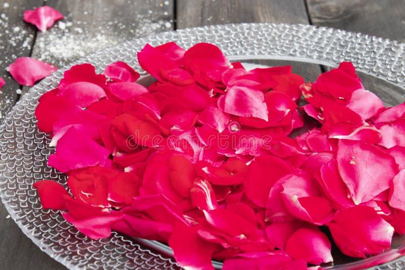 Rosa kronblad ligger på en platta på gamla mörka träbräden arkivfoto