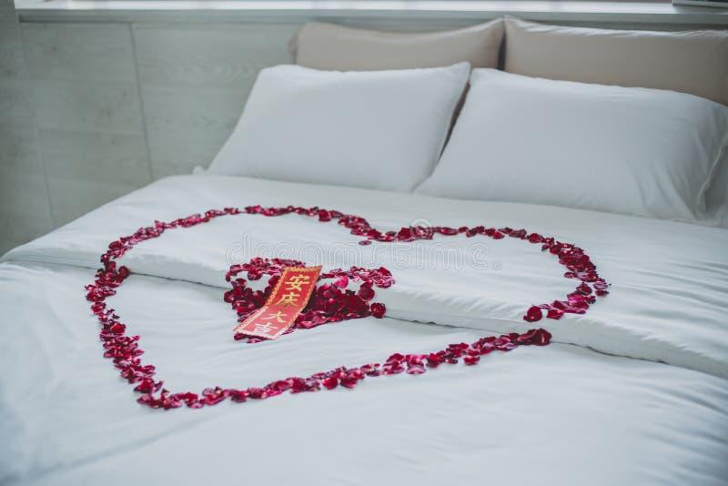 Rosa kronblad planlägger i hjärtaform på att gifta sig säng med facket i kinesisk gifta sig dag royaltyfria bilder