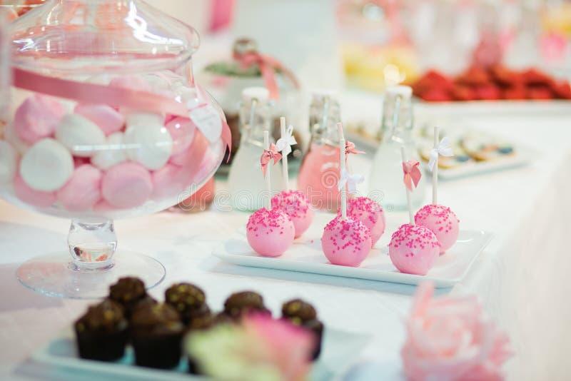 Rosa Kuchen knallt auf einer Nachtischtabelle lizenzfreie stockfotografie
