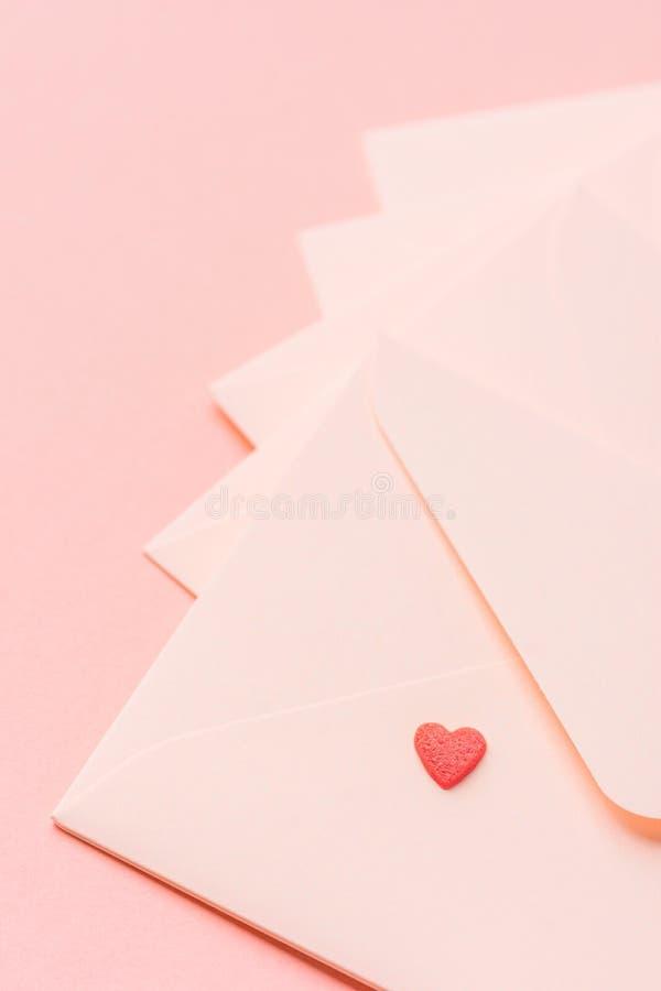 Rosa kuvert ordnade i fan med en liten röd godishjärta överst Monokrom peachy bakgrund Välgörenhet för valentinförälskelsebokstäv arkivbilder