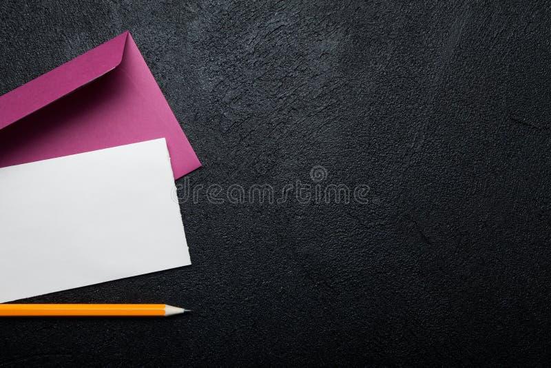 Rosa kuvert, tomt vitt ark av papper och blyertspenna på svart bakgrund Tomt avst?nd f?r text royaltyfri fotografi