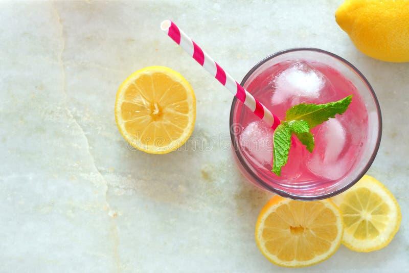 Rosa lemonad med mintkaramellen och citroner, över huvudet sikt på marmor royaltyfria foton