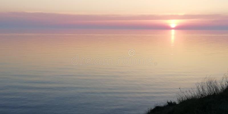 Rosa lindo e por do sol lilás sobre a extensão quieta do mar fotografia de stock royalty free