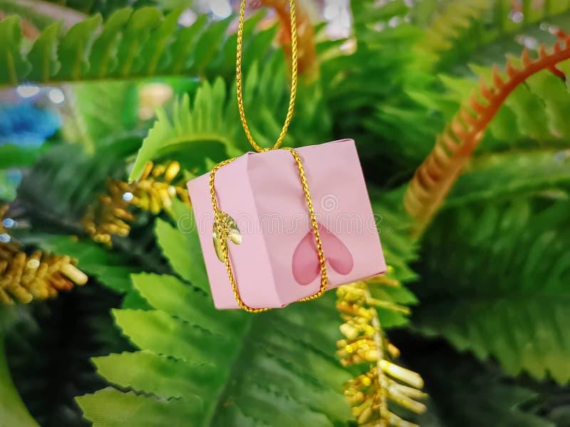 Rosa liten gåvaask som slås in med mönstrat papper för hjärta royaltyfria foton