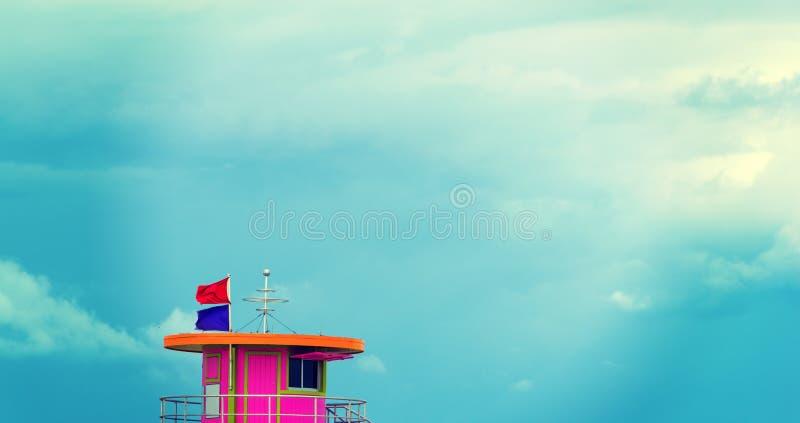 Rosa livräddarekoja under en mulen himmel i Miami Beach arkivbild