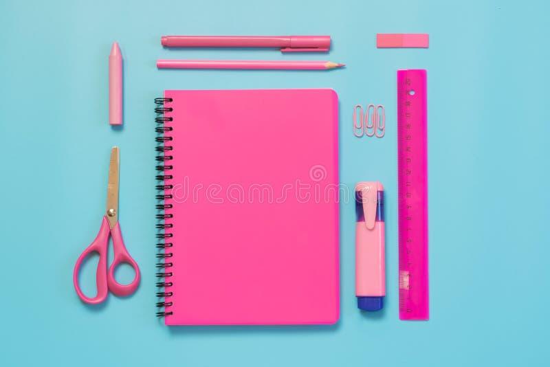 Rosa mädchenhafter Schulbedarf, Notizbücher und Stifte auf schlagkräftigem Blau Draufsicht, flache Lage Kopieren Sie Platz lizenzfreie stockfotografie