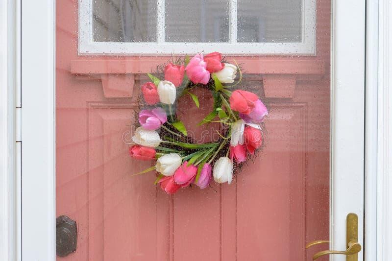 Rosa målad dörr med kransen av tulpan på en regnig dag arkivbild