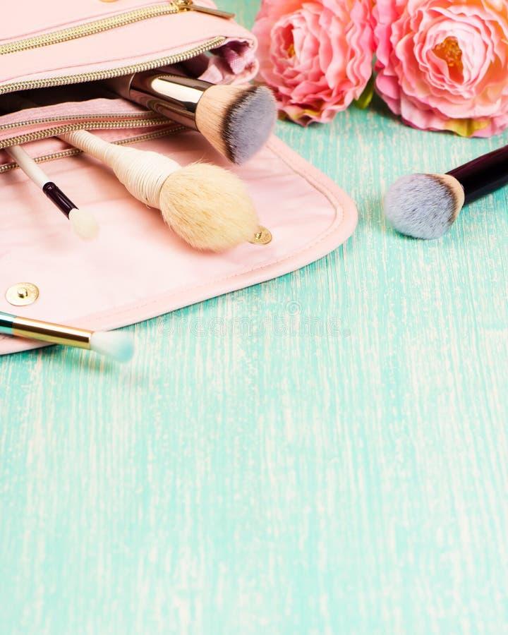 Rosa makeuppåse med brashes och dekorativa skönhetsmedel på det kvinnliga skrivbordet royaltyfria bilder