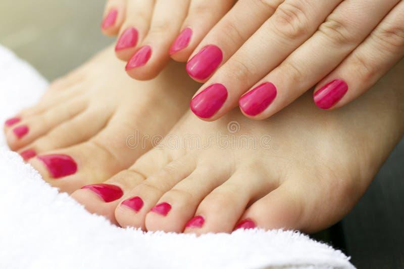 Rosa manikyr och pedikyr på kvinnliga händer och ben, närbild, sidosikt arkivfoton