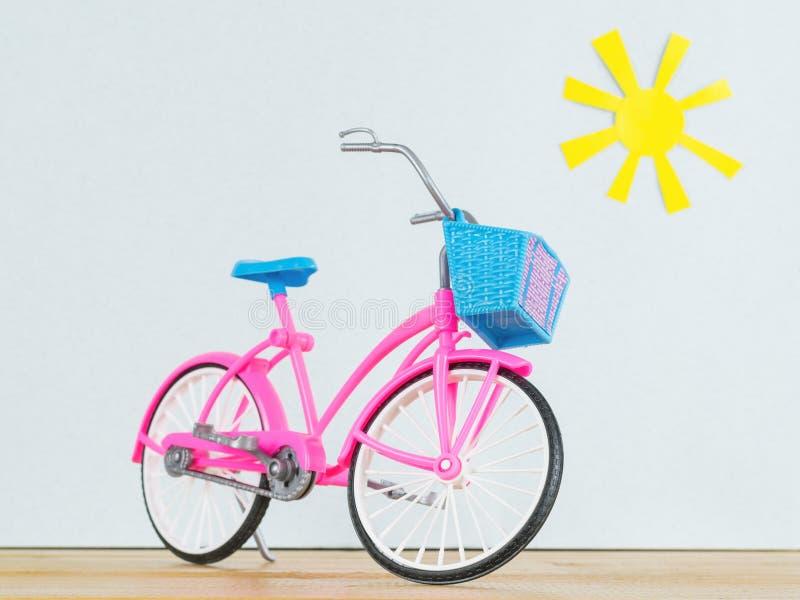 Rosa Modell von Kind-` s Fahrrad auf dem Bretterboden vor dem hintergrund der Spielzeugsonne lizenzfreie stockbilder